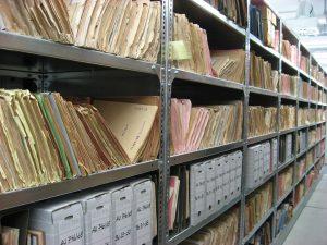 Auf dem Foto ist ein Regal mit archivierten Akten zu sehen.