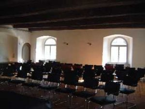 Auf dem Foto ist ein Raum mit Stühlen im Gebäude des Ledenhofes zu sehen.