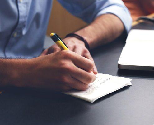 Auf dem Foto ist eine Hand zu sehen, die einen Text schreibt.