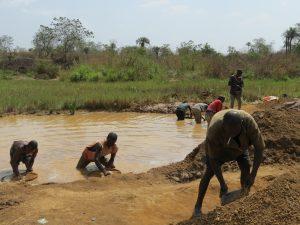 Auf dem Foto sind einig Männer zu sehen, die an einem See nach Diamanten schürfen.