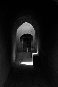 Au dem Schwarzweißfoto ist ein langer Gang mit Schatten und Licht zu sehen.