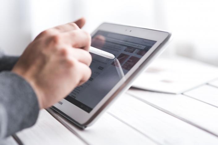 Auf dem Foto ist eine Hand zu sehen, die ein Tablet bedient.