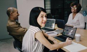 Auf dem Bild sind drei Menschen mit ihren Laptops an einem Tisch zu sehen.