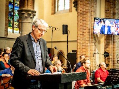 Auf dem Foto ist ein Redner hinter einem Pult zu sehen.