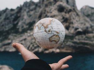 Auf dem Foto ist eine Hand zu sehen, die einen Globus hält.